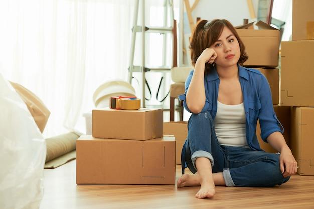 Plano completo de mujer cansada sentada en el suelo junto a cajas de embalaje