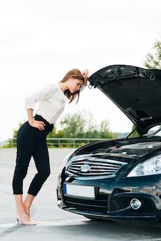 Plano completo de mujer comprobando motor
