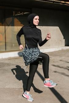 Plano completo de mujer con entrenamiento de hijab