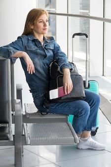 Plano completo de mujer esperando su vuelo