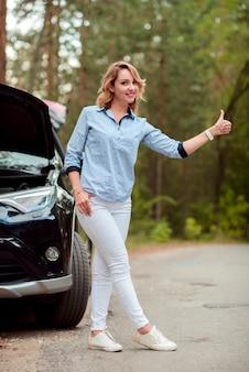 Plano completo de una mujer haciendo autostop