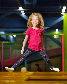 Plano completo de niña encantadora saltando
