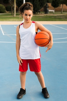 Plano completo de niña con pelota de baloncesto