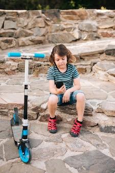 Plano completo del niño mirando el teléfono