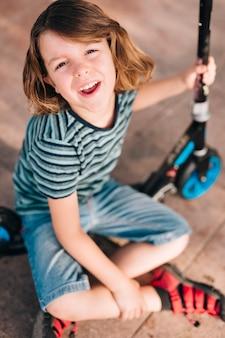 Plano completo del niño con scooter