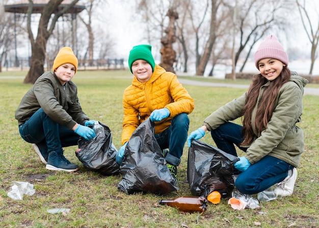 Plano completo de niños reciclando en el suelo