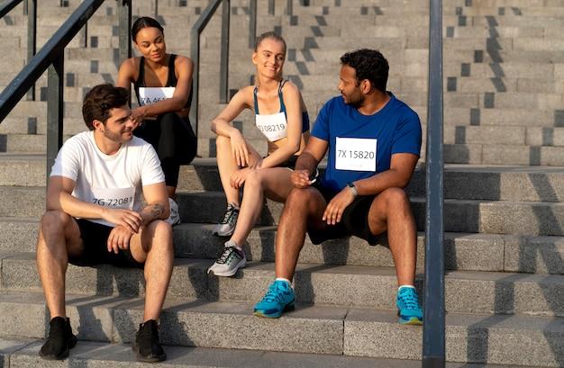 Plano completo personas sentadas en las escaleras