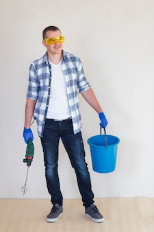 Plano completo del trabajador sosteniendo un balde