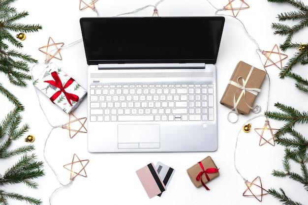 Plano de compras en línea de navidad. una computadora portátil abierta, una tarjeta de crédito, cajas de regalo atadas con una cinta roja, ramas de abeto verde, guirnaldas de estrellas