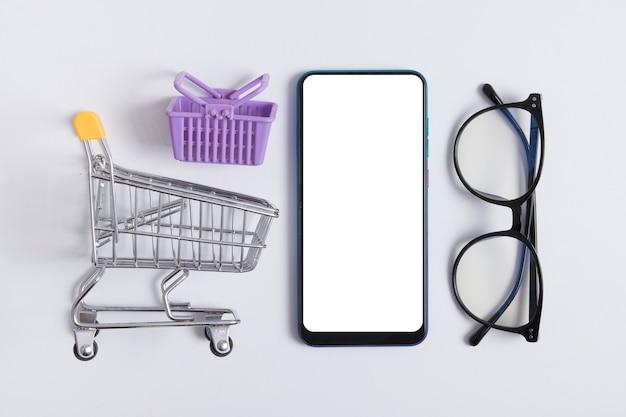 Plano de compras en línea con teléfono, carrito de supermercado y gafas