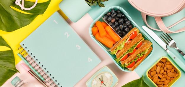 Plano creativo con almuerzo saludable y útiles de oficina.