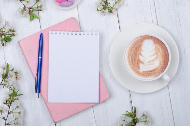 Plano creativo de escritorio, bloc de notas y objetos de estilo de vida sobre fondo de madera.