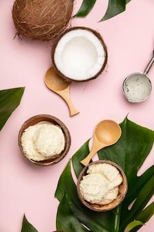 Plano creativo con helado de coco y plantas tropicales