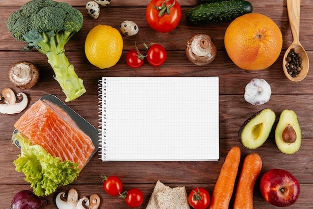 Plano de cuaderno con muchas verduras y salmón