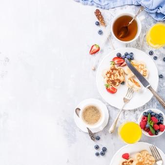 Plano con desayuno con panqueques escoceses en forma de flor, bayas y miel en una mesa de madera clara. concepto de comida sana con espacio de copia.