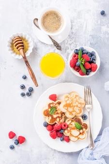 Plano con desayuno con panqueques escoceses en forma de flor, bayas y miel en una mesa de madera clara. concepto de comida sana