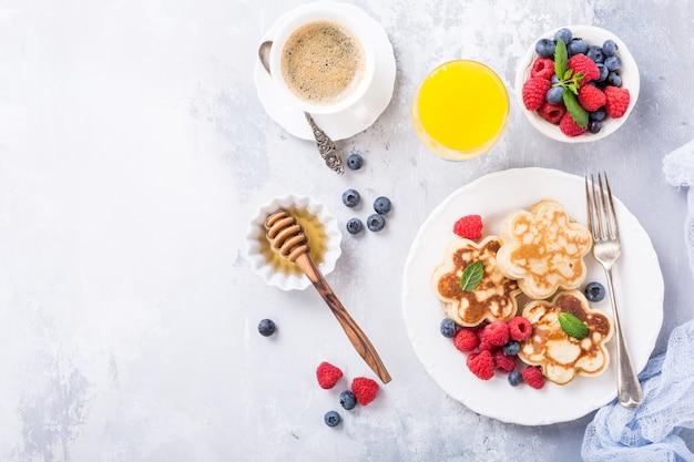 Plano con desayuno con panqueques escoceses en forma de flor, bayas y miel en una mesa de madera clara.
