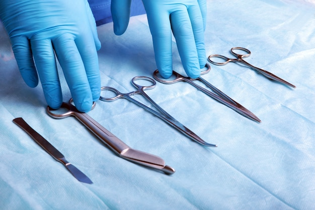 Plano de detalle de instrumentos de cirugía esterilizados con una mano agarrando una herramienta