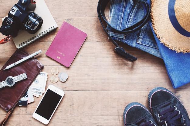 Plano de la disposición de los artículos de treveler, accesorios de vacaciones esenciales de joven inteligente viajero, concepto de viaje sobre fondo de madera