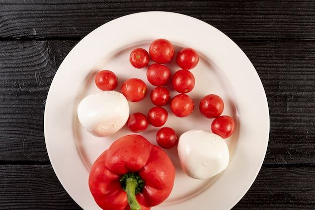 Plano de disposición de tomates y pizza en mesa de madera