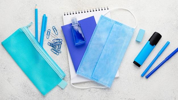 Plano de elementos esenciales de la escuela con cuaderno y máscara médica