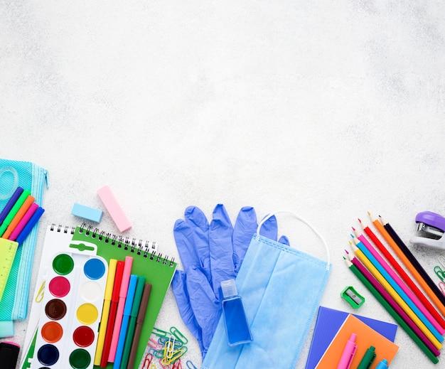Plano de elementos esenciales de la escuela con cuadernos y máscara médica
