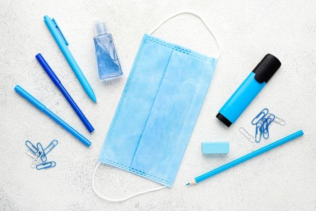 Plano de elementos esenciales de la escuela con lápices y máscara médica