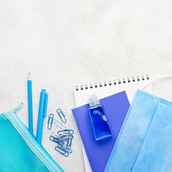 Plano de elementos esenciales de la escuela con máscara médica y clips de papel