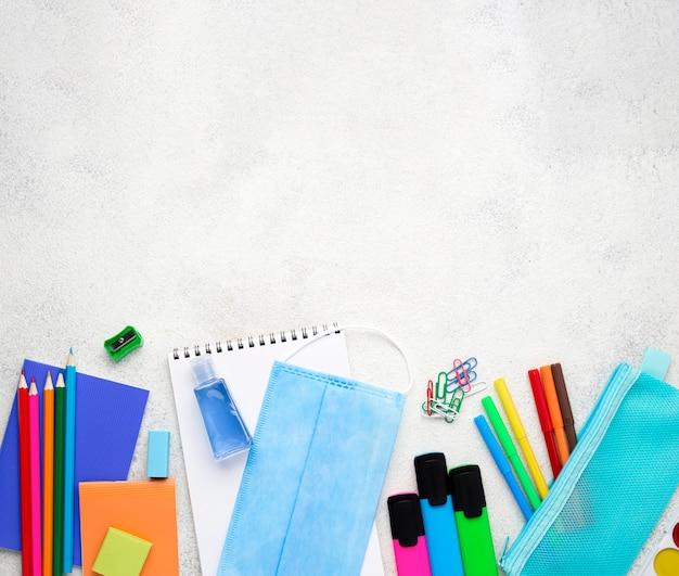 Plano de elementos esenciales de la escuela con máscara médica y espacio de copia