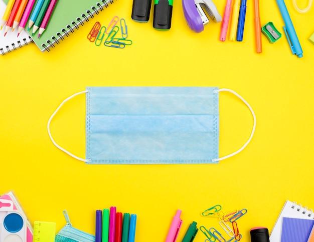 Plano de elementos esenciales de la escuela con máscara médica y lápices de colores.