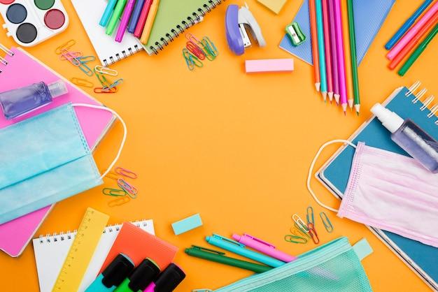 Plano de elementos esenciales de la escuela con máscaras médicas y lápices de colores.