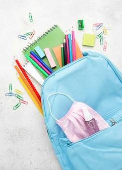 Plano de elementos esenciales de la escuela con mochila y máscara médica