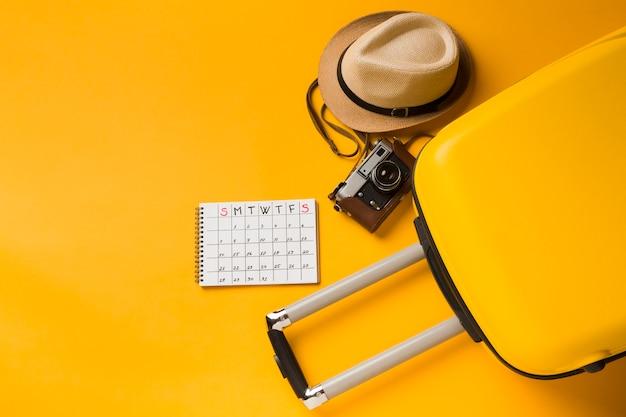 Plano de equipaje con sombrero y elementos esenciales de viaje