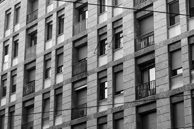 Plano en escala de grises de un edificio largo con ventanas y balcones