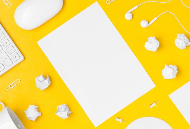 Plano de espacio de trabajo de escritorio con hoja de papel de espacio en blanco sobre fondo amarillo