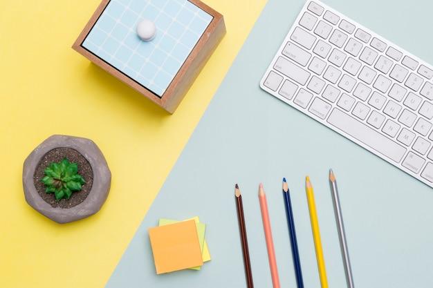 Plano del espacio de trabajo con teclado y lápices.