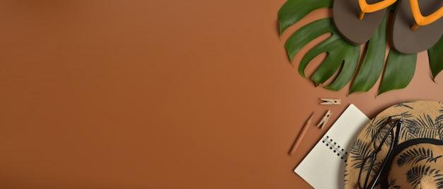 Plano, espacio de trabajo de vista superior con gafas, cuaderno, sombrero, lápiz, hoja verde, zapatos y taza de café sobre fondo marrón.
