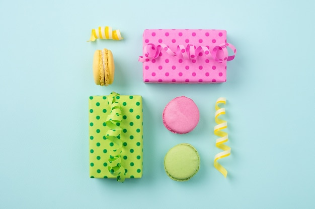 Plano festivo con cajas de regalo y coloridos macarons en una superficie azul claro