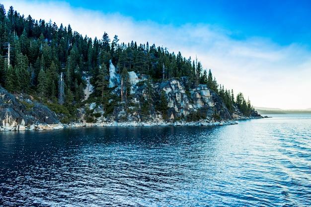 Plano general de un mar azul claro cerca de una montaña cubierta de pinos bajo un cielo despejado