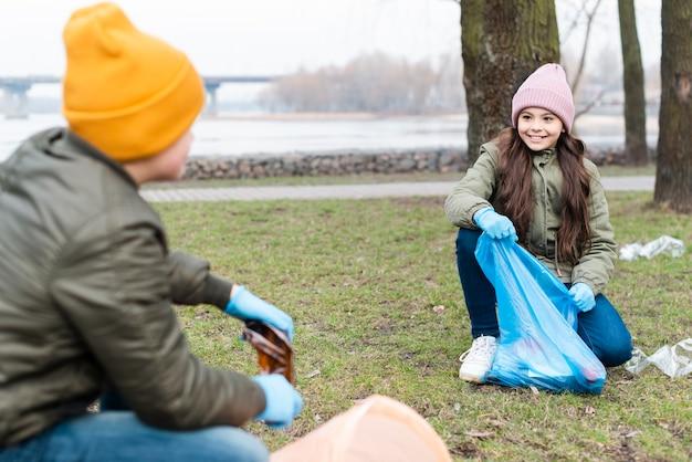 Plano general de niños limpiando el suelo
