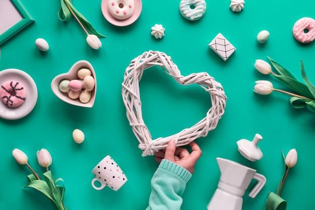El plano geométrico de primavera yacía en blanco y verde en la pared rosa pascua, día de la madre, cumpleaños de primavera o aniversario. tablero de luz de plástico, huevos de pascua, cafetera, tazas, tulipanes, regalos.