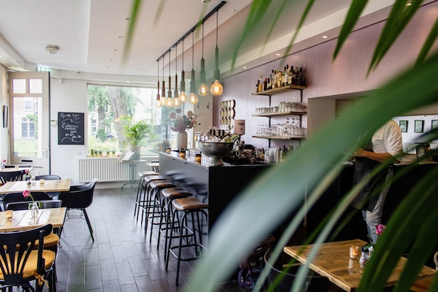 Plano interior de un café con sillas cerca del bar con mesas de madera.