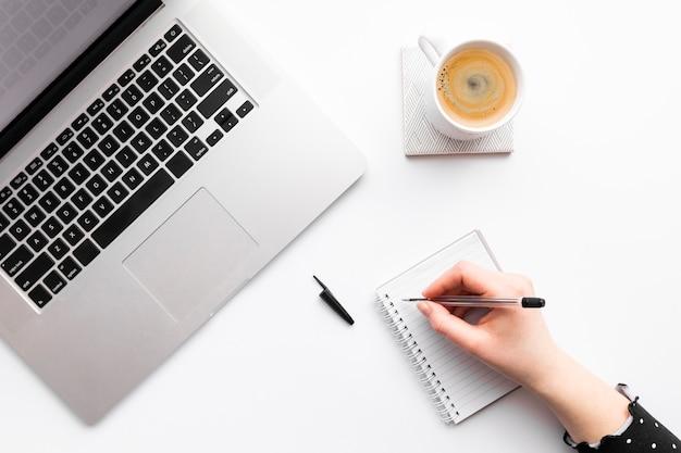 Plano laico arreglo comercial creativo sobre fondo blanco con persona tomando notas