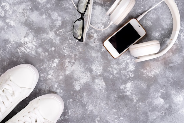 Plano lay de zapatillas blancas sobre fondo de piedra con teléfono y auriculares.
