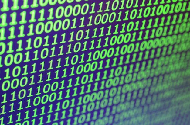 Plano macro de código binario en el monitor de una computadora de oficina