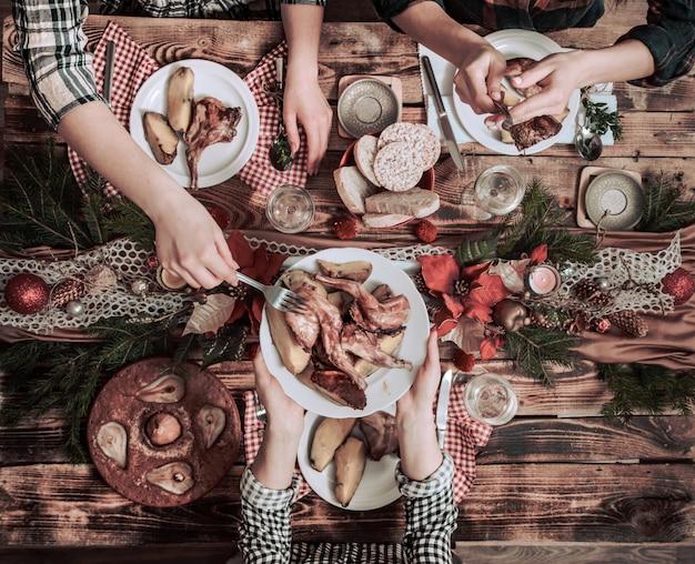 Plano de manos de amigos comiendo y bebiendo juntos. vista superior de personas que tienen fiesta, reunión, celebrando juntos en la mesa rústica de madera