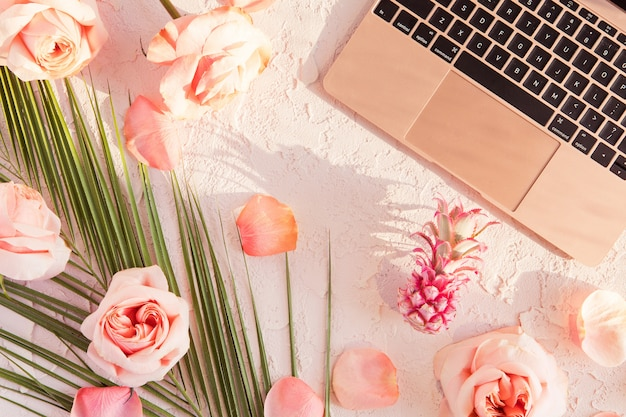 Plano de maqueta de espacio de trabajo tropical con computadora portátil moderna, hojas de palma monstera, flores rosadas, piña exótica y pétalos sobre pastel