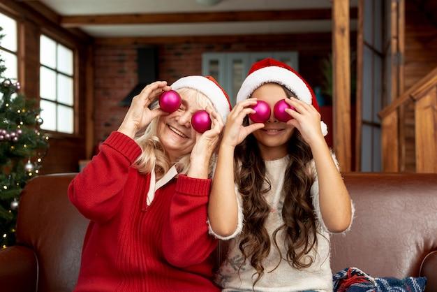 Plano medio abuela y niño posando con bolas de navidad
