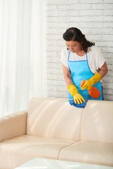 Plano medio del ama de llaves femenina que limpia el sofá de cuero