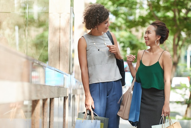 Plano medio de amigas asiáticas conversando en el centro comercial